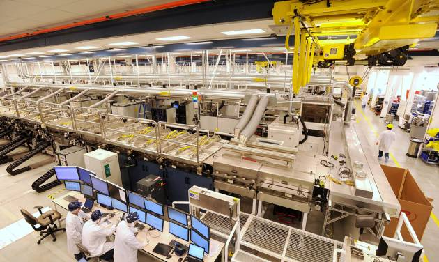FILE - In this Oct. 6, 2010 file photo, workers monitor a control bank at Solyndra's solar panel factory on in Fremont, Calif.  Homeowners on the hunt for sparkling solar panels are lured by ads filled with images of pristine landscapes and bright sunshine, and words about the technology's benefits for the environment _ and the wallet. What customers may not know is that there's a dirtier side.  While solar is a far less polluting energy source than coal, many panel makers are nevertheless grappling with a hazardous waste problem. Fueled partly by billions in government incentives, the industry is creating millions of solar panels each year and, in the process, millions of pounds of polluted sludge and contaminated water. (AP Photo/Noah Berger, File)