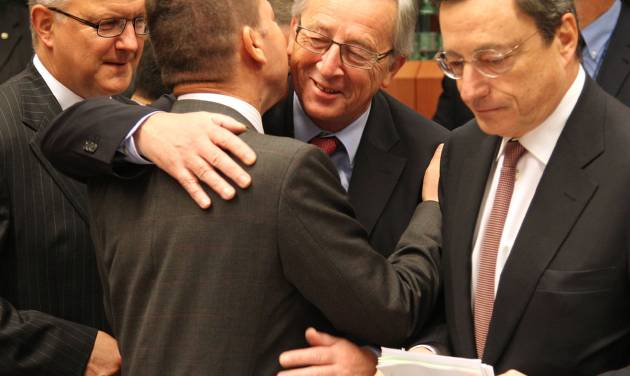 """Luxembourg's Prime Minister and chairman of the Eurogroup Jean-Claude Juncker, second right, greets Greek Finance Minister Yannis Stournaras, second left, as European Commissioner for Economic and Monetary Affairs Olli Rehn, left, and President of the European Central Bank Mario Draghi, right, look on, during the Eurogroup finance ministers meeting in Brussels, Monday, Nov, 12, 2012. Greece's international lenders have prepared a """"positive"""" report on the country's reform efforts, a crucial step in its efforts to secure the next installment of its bailout loan, the head the of group of finance ministers from the 17 euro countries said Monday. (AP Photo/Yves Logghe)"""