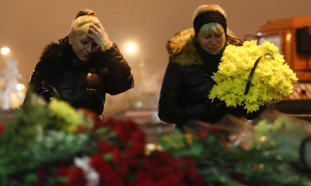 Women cry laying flowers outside the Volgograd main railway station in Volgograd, Russia, early Monday Dec. 30, 2013. Russian authorities ordered police to beef up security at train stations and other facilities across the country after a suicide bomber killed 14 people on a bus Monday in the southern city of Volgograd.It was the second deadly attack in two days on the city that lies just 400 miles (650 kilometers) from the site of the 2014 Winter Olympics. (AP Photo/Denis Tyrin)