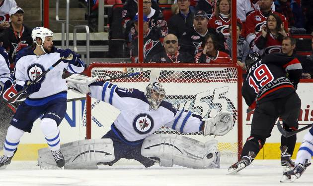 Carolina Hurricanes' Jiri Tlusty (19) of the Czech Republic has his shot blocked by Winnipeg Jets goalie Ondrej Pavelec (31) of the Czech Republic,  with Jets Zach Bogosian (44) nearby during the first period of an NHL hockey game, Tuesday, March 26, 2013, in Raleigh, N.C. (AP Photo/Karl B DeBlaker)