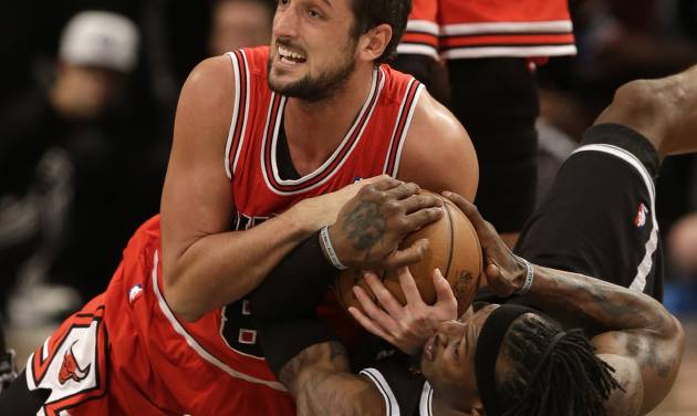 Chicago Bulls' Marco Belinelli, top, and Brooklyn Nets' Gerald Wallace fight for a loose ball during the second half of Game 1 in the first round of the NBA basketball playoffs at the Barclays Center, Saturday, April 20, 2013, in New York. The Nets defeated the Bulls 106-89. (AP Photo/Seth Wenig)
