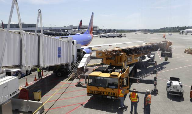A large crane stands ready to lift a jetway, right, that had a mechanical failure and slowly lowered to the ground Tuesday, May 13, 2014, while connected to a Southwest Airlines airplane at Seattle-Tacoma International Airport. The incident happened as passengers from Phoenix were deplaning. The next leg of the flight to Chicago had to be canceled so the jetway could be removed from the airplane and a damage inspection could be completed. (AP Photo)