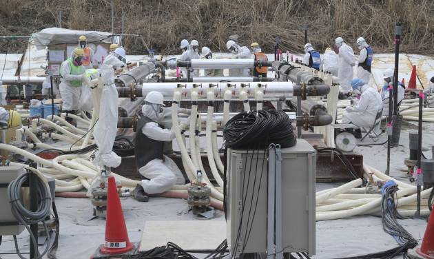 Workers of the Tokyo Electric Power Co. (TEPCO) wearing protective gears install underground frozen wall at the Fukushima Dai-ichi nuclear power plant in Okuma town, Fukushima prefecture, northeastern Japan, Monday, March 10, 2014. The radioactive water that has accumulated at the crippled nuclear power plant remains the biggest problem hampering the cleanup process three years after the disaster. (AP Photo/Koji Sasahara, Pool)