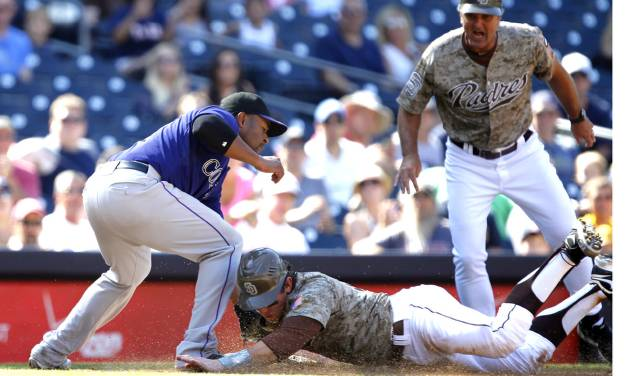 San Diego Padres' John Baker, center, beats the tag by Colorado Rockies third baseman Chris Nelson, left, as Padres third base coach Glenn Hoffman looks on during the fifth inning of their baseball game in San Diego, Sunday, Sept. 16, 2012. (AP Photo/Alex Gallardo)