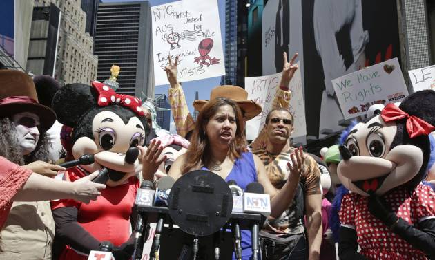 """Lucia Gomez, center, executive director of La Fuente, speaks during a press conference, Tuesday, Aug. 19, 2014 at Times Square in New York. Gomez lead the gathering that called for the fair treatment and the right for performers to work as costumed characters. Gomez said, """"These are individuals who bring smiles to the world."""" (AP Photo/Vanessa A. Alvarez)"""