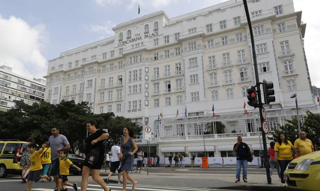 Pedestrians cross a street in front of the Copacabana Palace where Ray Whelan, of MATCH Services, is staying, in Rio de Janeiro, Brazil, Tuesday, July 8, 2014. The World Cup corporate hospitality executive was arrested at the Copacabana Palace Monday, the hotel used by FIFA officials during the World Cup. Whelan, who is suspected of involvement with a ticket-scalping ring, was released from prison early Tuesday. (AP Photo/Leo Correa)