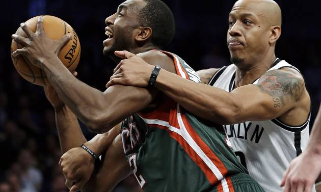 FILE - In this Feb. 19, 2013, file photo, Brooklyn Nets forward Keith Bogans, right, fouls Milwaukee Bucks forward Luc Richard Mbah a Moute (12) during an NBA basketball game in New York. The Bucks traded forward Mbah a Moute to the Sacramento Kings in exchange for a 2016 second-round draft pick, a person familiar with the deal said Tuesday, July 9, 2013. The person, who spoke on condition of anonymity to The Associated Press because teams can't confirm moves until the new league year begins Wednesday, also said Milwaukee has the right to swap 2018 second-round picks. (AP Photo/Kathy Willens, File)