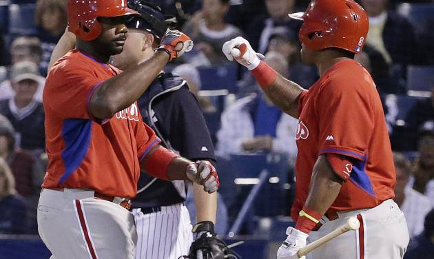 Philadelphia Phillies' Ryan Howard greets on-deck batter Marlon Byrd at the plate after hitting a third-inning solo home run off New York Yankees relief pitcher Vidal Nuno in an exhibition baseball game in Tampa, Fla., Tuesday, March 25, 2014. Nuno also allowed a solo home run to Byrd in the inning. Yankees catcher Brian McCann is at left rear. AP Photo/Kathy Willens)