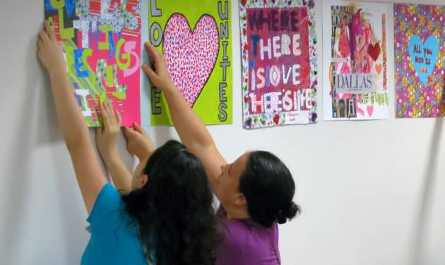 Brenda Castaneda, left, and Irma Castaneda, right, help the nonprofit art organization 29 Pieces hang art in the hallways at Parkland Memorial Hospital, Saturday Sept. 21, 2013 in Dallas. About 30,000 works of art reflecting on love will be displayed throughout Dallas this fall to commemorate the 50th anniversary of the assassination of President John F. Kennedy. (AP Photo/29 Pieces)