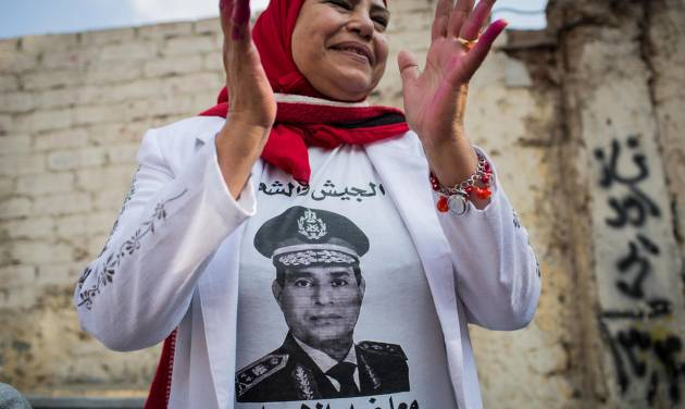 """An Egyptian woman wears a t-shirt with a photo of Egypt's Defense Minister, Gen. Abdel-Fattah el-Sissi outside a polling station on the first day of voting in the country's constitutional referendum in Cairo, Egypt, Tuesday, Jan. 14, 2014. Upbeat and resentful of the Muslim Brotherhood, Egyptians voted Tuesday on a new constitution in a referendum that will pave the way for a likely presidential run by the nation's top general months after he ousted Islamist President Mohammed Morsi. Arabic on her shirt reads, """"the military and the people together against terrorism.""""(AP Photo/Eman Helal)"""