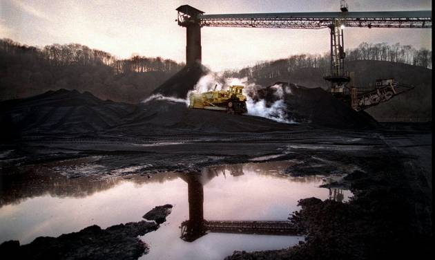 FILE - In this Dec. 19, 1997 file photo, a bulldozer pushes coal to a waiting train at the Powhatan No. 6 mine in Alledonia, Ohio. The Ohio EPA has allowed more than a dozen coal facilities' discharge permits, including Powhatam No. 6's, to expire since Republican Gov. John Kasich took office in 2011. (AP Photo/The Plain Dealer, Scott Shaw, File) MANDATORY CREDIT; NO SALES