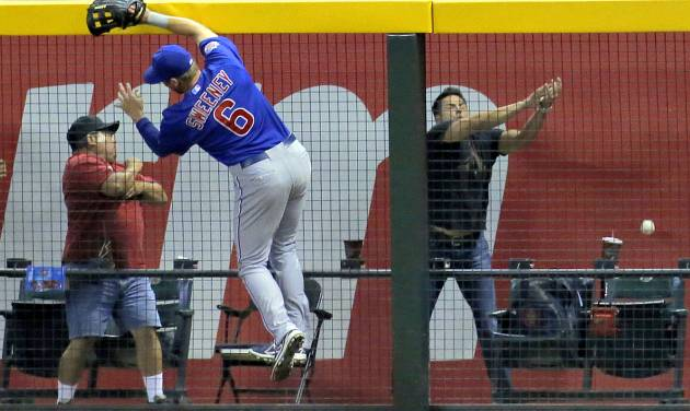 Chicago Cubs' Ryan Sweeney (6) can't catch a solo home run hit by Arizona Diamondbacks' Paul Goldschmidt during the sixth inning of a baseball game, Friday, July 18, 2014, in Phoenix. (AP Photo/Matt York)