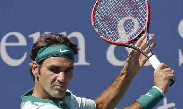 Roger Federer, from Switzerland, eyes a backhand against Vasek Pospisil, from Canada, during a match at the Western & Southern Open tennis tournament, Wednesday, Aug. 13, 2014, in Mason, Ohio. (AP Photo/Al Behrman)