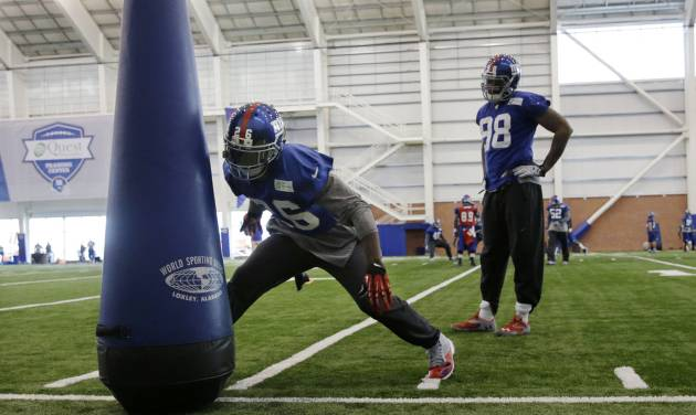 New York Giants defensive end Damonte Moore (98) looks on as safety Antrel Rolle (26) hits a practice dummy during NFL football practice in East Rutherford, N.J., Wednesday, Nov. 20, 2013. AP Photo/Mel Evans)
