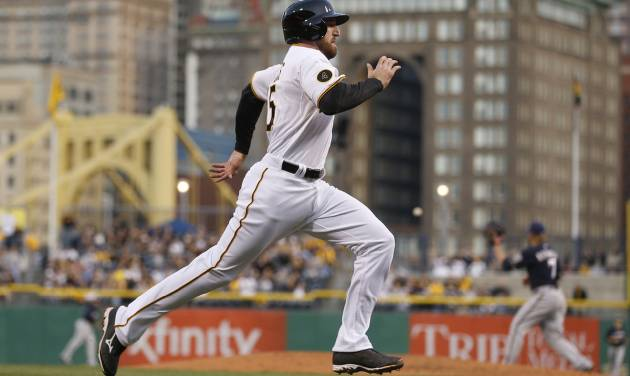 Pittsburgh Pirates' Ike Davis heads home to score from second on a hit by Neil Walker as Milwaukee Brewers first baseman Mark Reynolds, right, waits for the throw from center field in the second inning of a baseball game Saturday, April 19, 2014, in Pittsburgh. (AP Photo/Keith Srakocic)