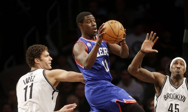 Philadelphia 76ers' Jrue Holiday, center, looks to pass past Brooklyn Nets' Brook Lopez, left, and Gerald Wallace during the first half of an NBA basketball game at the Barclays Center Sunday, Dec. 23, 2012 in New York.  (AP Photo/Seth Wenig)