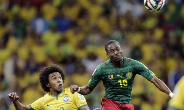 Brazil's Willian watches as Cameroon's Vincent Aboubakar heads the ball during the group A World Cup soccer match between Cameroon and Brazil at the Estadio Nacional in Brasilia, Brazil, Monday, June 23, 2014. (AP Photo/Bernat Armangue)