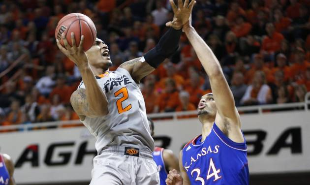 Oklahoma State wing Le'Bryan Nash (2) shoots in front of Kansas forward Perry Ellis (34) during the second half of an NCAA college basketball game in Stillwater, Okla., Saturday, March 1, 2014. Oklahoma State won 72-65. (AP Photo/Sue Ogrocki)