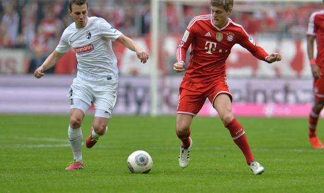 Bayern's Toni Kroos, right, and Freiburg's Vladimir Darida of Czech Republic challenge for the ball during the German first division Bundesliga soccer match between  FC Bayern Munich and SC Freiburg in Munich, Germany, on Saturday, Feb. 15, 2014. (AP Photo/Kerstin Joensson)