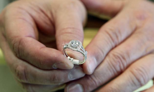 In this May 14, 2014 photo, Brad Padgett, owner of Bradley's Jewelers, shows off one of his favorite engagement rings in Jacksonville, N.C.  The answer to the question of how much to spend on an engagement ring rests in striking a balance between a ring that will dazzle your beloved without tarnishing your future financial goals together. (AP Photo/The Daily News, Maria Sestito)