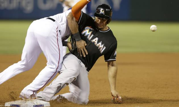 Miami Marlins Giancarlo Stanton, right, slides safely into third base against Texas Rangers third baseman Adrian Beltre (29) during the eighth inning of a baseball game in Arlington, Texas, Tuesday, June 10, 2014. Stanton reached base on a single by teammate Casey McGehee. (AP Photo/LM Otero)