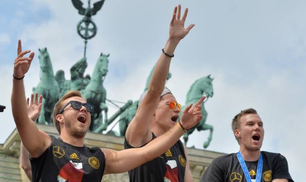 """German  soccer players  Mario Goetze, left,  Julian Draxler ,center,  and  Kevin Großkreutz  celebrate in front of the Brandenburg Gate in Berlin, Tuesday July 15, 2014.  Germany's World Cup winners shared their fourth title with hundreds of thousands of fans by parading the trophy through cheering throngs to celebrate at the Brandenburg Gate on Tuesday. An estimated 400,000 people packed the """"fan mile"""" in front of the Berlin landmark to welcome home coach Joachim Loew's team and the trophy — which returned to Germany for the first time in 24 years.  (AP Photo/dpa,Hendrik Schmidt)"""
