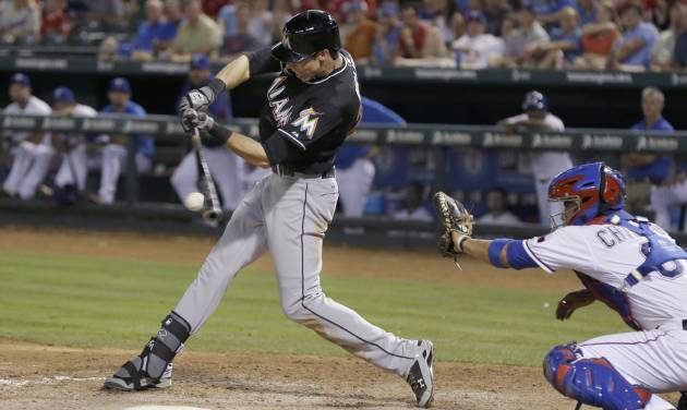 Miami Marlins Christian Yelich, left, hits a two run RBI single in front of Texas Rangers catcher Robinson Chirinos (61)  during the seventh inning of a baseball game in Arlington, Texas, Tuesday, June 10, 2014. Marlins Justin Bour and Jeff Mathis scored on the play.  (AP Photo/LM Otero)