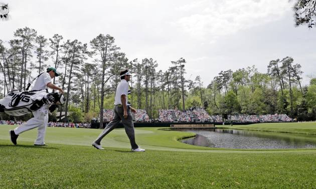 Bubba Watson walks with his Ted Scott down the 15th fairway during the second round of the Masters golf tournament Friday, April 11, 2014, in Augusta, Ga. (AP Photo/David J. Phillip)