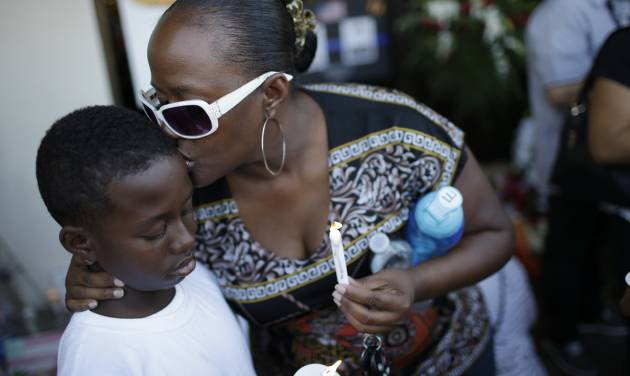 Tiffany Moore kisses her son Elijah Unce, 10, during a vigil at a CiCi's Pizza Monday, June 9, 2014 in Las Vegas. The vigil was held to honor two Las Vegas Metropolitan Police officers and a bystander who were killed Sunday. (AP Photo/John Locher)