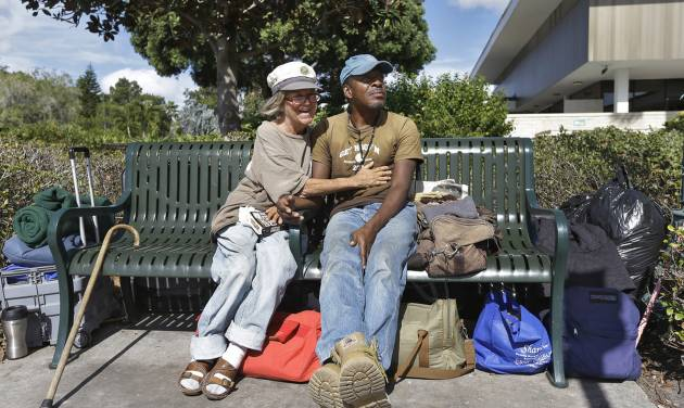 In a Friday, Jan. 11, 2013 photo, Cindy Edlund, left, and James Franklin Jr., both of whom are homeless, spend the day on a bench outside the Sarasota City Hall Friday, Jan. 11, 2013, in Sarasota, Fla. Newer, wealthy residents in the Gulf Coast city known for its arts scene and beautiful beaches are buying expensive downtown condos so they can live an urban lifestyle _ but don't want the problems associated with a city, including the 700 or so homeless people who inhabit the county, the American Civil Liberties Union and others contend. (AP Photo/Chris O'Meara)