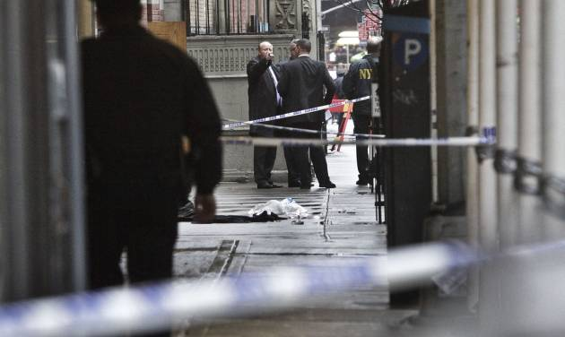 Police investigate the scene where a man was fatally shot in the back of the head in New York on Monday, Dec. 10, 2012. Authorities said the man was shot outside a school near Columbus Circle in Manhattan, lying mortally wounded in a pool of blood as the suspect escaped with a getaway driver. (AP Photo/Bebeto Matthews)