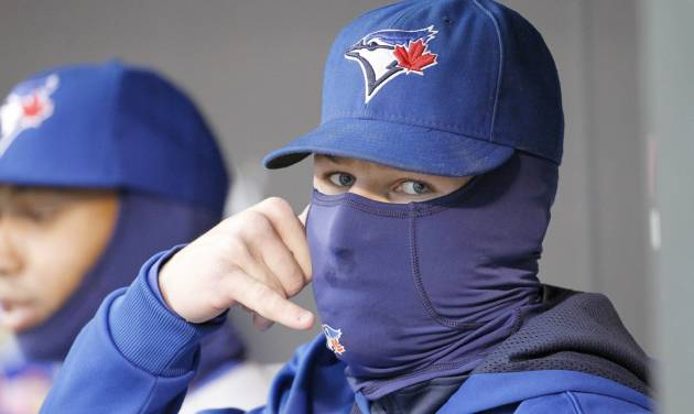 Toronto Blue Jays third baseman Brett Lawrie imitates talking on a phone as he sits bundled up in the dugout during the first inning of the MLB American League baseball game against the Minnesota Twins where the temperature was 36 degrees at game time in Minneapolis, Tuesday, April 15, 2014.  (AP Photo/Ann Heisenfelt)
