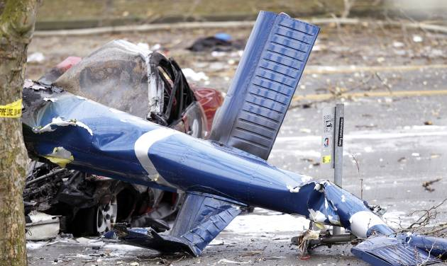FILE - The wreckage of a news helicopter sits on a city street after crashing in this March 18, 2014 file photo taken in Seattle. The surveillance footage taken from three security camera recordings near the crash site shows the aircraft began rotating counterclockwise during takeoff Tuesday morning and rose slightly, nearly level, from a rooftop helipad, the agency said late Friday night March 21, 2014 in a preliminary report. (AP Photo/Stephen Brashear)