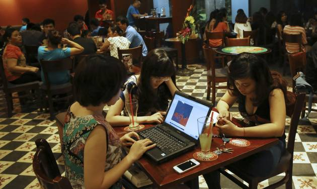 FILE - In this May 14, 2013 photo, three young Vietnamese women use a laptop and smart phones to go online at a cafe in Hanoi, Vietnam. Vietnamese pro-democracy activists and bloggers are battling a gathering campaign of blocking, hacking and spying by a shadowy pro-government army of cyber warriors. Although they can't prove it, activists and analysts strongly suspect the Vietnamese state is involved in the campaign, which is hampering the country's democracy movement. (AP Photo/Na Son Nguyen, File)