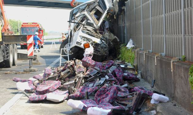 The wreckage of a destroyed bus is left on a highway in Fujioka, Gunma prefecture, north of Tokyo Sunday, April 29, 2012. Police say the bus carrying dozens of holiday makers crashed on the highway while heading for Tokyo Disneyland, killing at least seven people and injuring dozens. (AP Photo/Kyodo News) JAPAN OUT, MANDATORY CREDIT, NO LICENSING IN CHINA, HONG KONG, JAPAN, SOUTH KOREA AND FRANCE