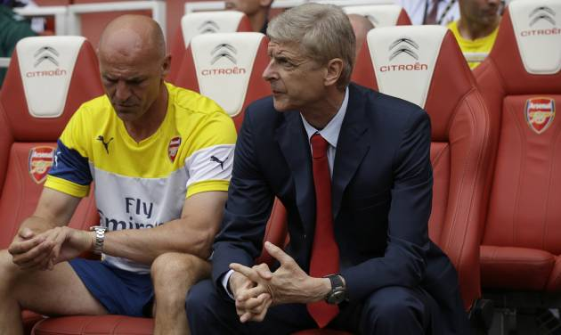 Arsenal's French manager Arsene Wenger, right, sits with his assistant Steve Bould before the start of the Emirates Cup soccer match between between Arsenal and Benfica at Arsenal's Emirates Stadium in London, Saturday, Aug. 2, 2014.  (AP Photo/Matt Dunham)