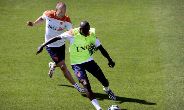 Arjen Robben, left, and Bruno Martins Indi, right, from the Netherlands soccer team run after the ball during a training session in Rio de Janeiro, Brazil, Sunday June 8, 2014.  The Netherlands play in group B of the 2014 soccer World Cup. (AP Photo/Wong Maye-E)
