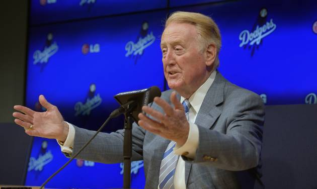 Los Angeles Dodgers announcer Vin Scully speaks to the media prior to a baseball game against the Atlanta Braves, Wednesday, July 30, 2014, in Los Angeles. The 86-year-old Hall of Fame announcer said Tuesday that he will return for his record 66th season with the team in 2015. (AP Photo/Mark J. Terrill)