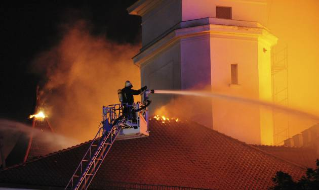 In this photo released by China's Xinhua Agency, a firefighter tries to extinguish blaze on the roof of Riga Castle, Latvia, Thursday, June 20, 2013. The Baltic News Service is reporting that a fire has partially damaged the Riga Castle, a medieval fortress that houses the National History Museum of Latvia. The castle normally serves as the presidential residence, but BNS says Latvian President Andris Berzins is staying elsewhere as the building is being renovated. (AP Photo/Xinhua, Guo Qun) NO SALES