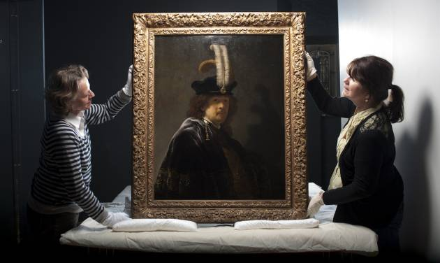 This undated handout photo provided by the National Trust shows Tina Sitwell, Paintings conservation advisor, left, and Patricia Pertnyk, House Steward, holding the self-portrait of Rembrandt which has returned to Buckland Abbey, Devon, England.  Scientific tests have confirmed that a painting donated to Britain's National Trust by a wealthy supporter is a Rembrandt self-portrait worth tens of millions of pounds (dollars). The painting was given to the heritage body in 2010 and hangs in Buckland Abbey in southwest England, former home of 16th-century seafarer Francis Drake. (AP Photo/ Steven Haywood/National Trust, PA) UNITED KINGDOM OUT