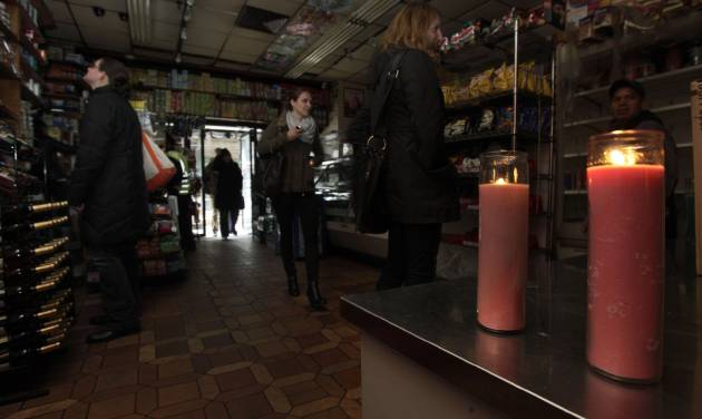 People shop in a candle-lit deli in New York's Tribeca neighborhood, Wednesday, Oct. 31, 2012. In lower Manhattan, some stores are open even though their power is still out. Others are busing essential employees to work. Days after superstorm Sandy hit, businesses both big and small are facing a tough choice, to reopen or stay closed.(AP Photo/Richard Drew)