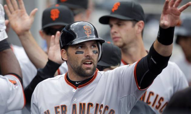 FILE - In this April 2, 2011, file photo, San Francisco Giants' Mark DeRosa is greeted by his teammates after scoring during a baseball game against the Los Angeles Dodgers in Los Angeles. DeRosa is retiring after a 16-year major league career. The Toronto Blue Jays announced DeRosa's decision in a statement Tuesday, Nov. 12, 2013, less than two weeks after Toronto exercised his $750,000 club option for next season. (AP Photo/Jae C. Hong, File)
