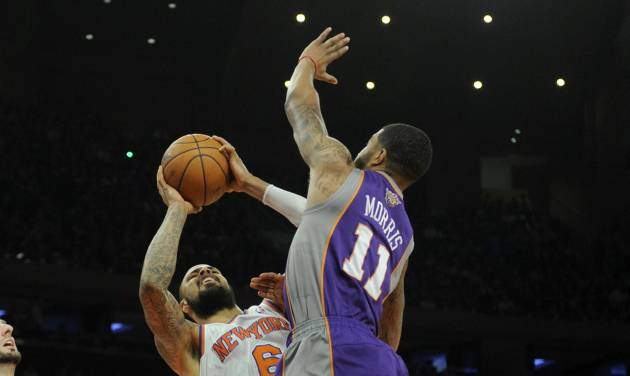 New York Knicks' Tyson Chandler, left, is fouled by Phoenix Suns' Markieff Morris in the first quarter of an NBA basketball game at Madison Square Garden in New York, Sunday, Dec. 2, 2012. (AP Photo/Henny Ray Abrams)