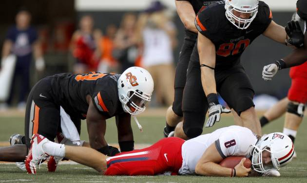 Oklahoma State's Nigel Nicholas (89) and Cooper Bassett (80) stand over Arizona's Nick Foles (8) after a sack during their game Thursday in Stillwater. PHOTO BY BRYAN TERRY, The Oklahoman