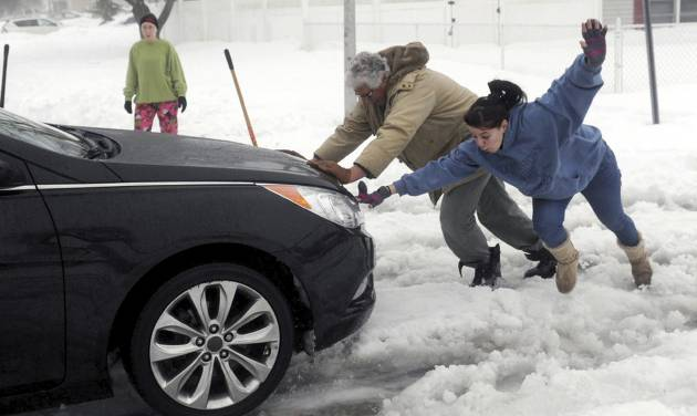 Candice Genega, right, loses her footing while helping Charlie McKenna push a stranded motorist out of heavy snow along an unplowed street in Centereach, N.Y. on Monday, Feb. 11,  2013. (AP Photo/Newsday, Thomas A. Ferrara) NYC OUT