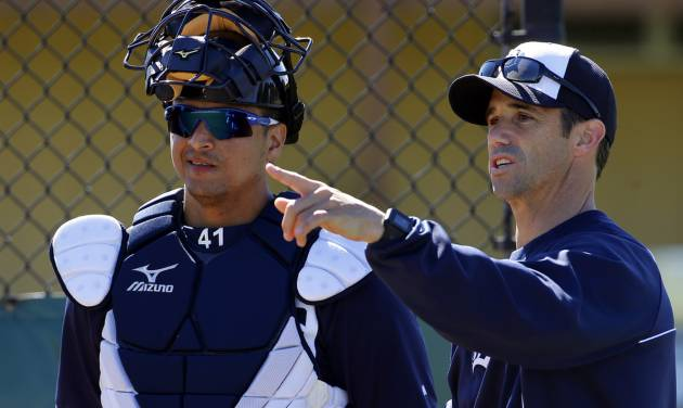 Detroit Tigers manager Brad Ausmus, right, talks with  Victor Martinez before a bullpen session on the team's first day of baseball spring training for pitchers and catchers, in Lakeland, Fla., Friday, Feb. 14, 2014. (AP Photo/Gene J. Puskar)