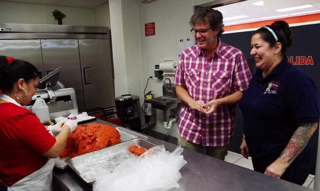 "This undated publicity image released by the Travel Channel shows George Motz, host of Travel Channel's new series ""Burger Land,""  at El Rey De Las Fritas, a restaurant in the Little Havana neighborhood of Miami, Fla. Motz crisscrosses the country looking for the best burgers in America. The series airs Mondays on the Travel Channel at 10 p.m. EST (AP Photo/Travel Channel)"