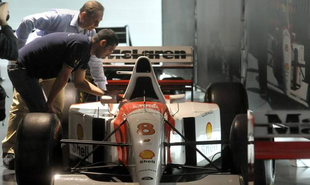Technicians checks a Mc Laren Formula One car driven by Ayrton Senna, on display at the the Imola track, Italy, Wednesday, April 30, 2014. Fans and family members are gathering this week to pay their respects to former Formula One drivers Ayrton Senna and Roland Ratzenberger on the 20th anniversary of their deaths. F1 drivers' chaplain Sergio Mantovani celebrated a memorial mass Wednesday in a packed room beside pit lane at the Enzo and Dino Ferrari track that once hosted the San Marino Grand Prix. (AP Photo/Marco Vasini)
