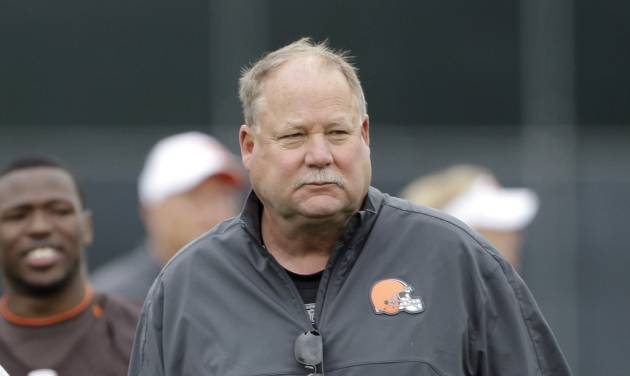 """FILE - In this June 5, 2012 file photo, Cleveland Browns president Mike Holmgren walks off the field following an off-season practice at the NFL football team's headquarters in Berea, Ohio. Holmgren says there are no plans """"right now"""" to move either quarterback Colt McCoy or Seneca Wallace before training camp. One of the two QBs will be rookie Brandon Weeden's backup. (AP Photo/Mark Duncan, File)"""
