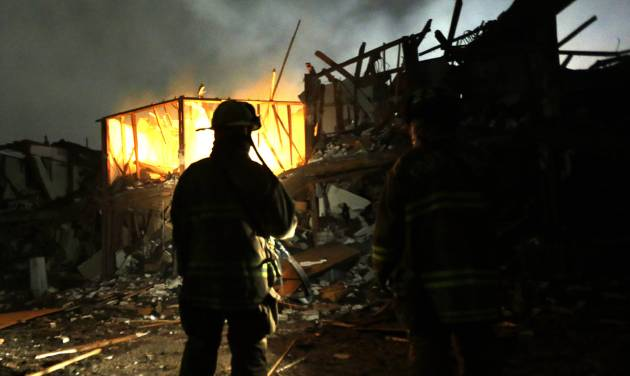 FILE - In this April 18, 2013, file photo, firefighters use flashlights to search a destroyed apartment complex near the West Fertilizer Co. plant that exploded in West, Texas. The Texas company that operated the fertilizer plant where a thunderous explosion in April killed 15 people is facing $118,300 in fines for two dozen serious safety violations, including a failure to have an emergency response plan, federal officials said Thursday, Oct. 10, 2013. (AP Photo/LM Otero, File)